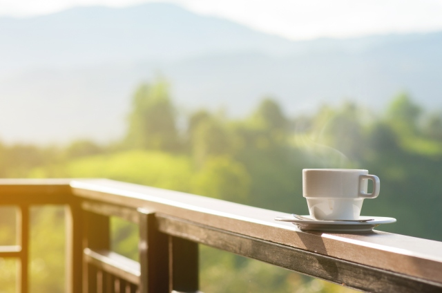 White cup of hot coffee with natural and mountains.
